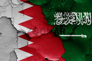flags of Bahrain and Saudi Arabia painted on cracked wall