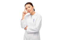 thinking asian female doctor in white coat