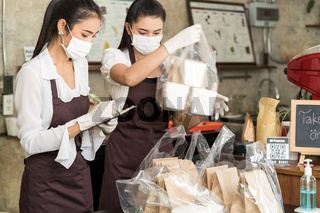 Waitress with face mask prepare order for curbside pick up and takeout.