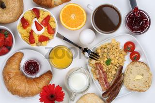 Frühstück mit Müsli, Kaffee, Rührei, Früchten und Brötchen von oben