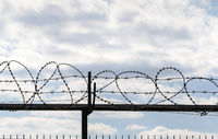 Coiled barbed wire fence and blue sky with clouds
