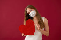 Cheerful woman with face mask showing red heart from front view.
