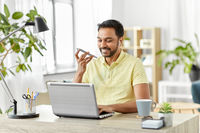 man recording voice on smartphone at home office