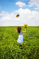 beautiful girl stands in the field with a bouquet of yellow flowers and throws her hat to the sky