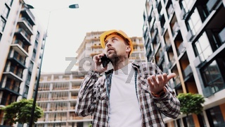 Angry male architect in orange hard hat talks swears on phone at construction site. Builder in plaid shirt emotionally displeased negotiates by cell phone. Screaming stressed architectural designer