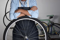 A bicycle repairman standing behind the wheel of a bike in his shop. Man is unrecognizable with his