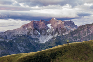 Man hiking on mountain and purple light illuminates landscape and the moody sky. Karkopf, Lechtal Alps, Austria.