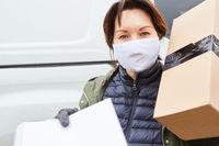 Paketbotin mit Mundschutz und Annahme Bestätigung