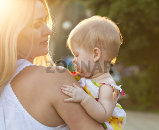 Mother and her baby enjoy the sunset