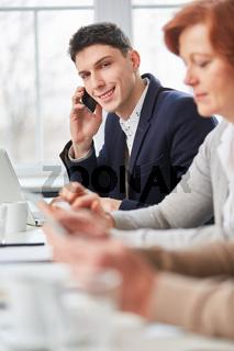 Geschäftsmann telefoniert mit Smartphone im Meeting