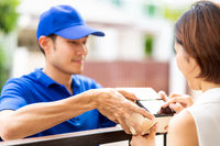 Asian customer woman sign on mobile phone for recieve package delivery.