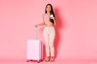 Travelling, holidays and vacation concept. Full-length of cheerful smiling asian girl tourist with suitcase, holding passport with flight tickets, heading to aiport to start journey, pink background
