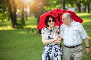 Happy elderly couple with umbrella. Handsome man and woman senior citizens. Husband and wife of old age for a walk.