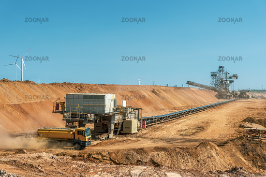 Truck at the end of a conveyor belt in the open pit.