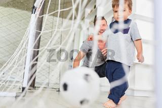 Kleinkind beim Fußball spielen im Wohnzimmer