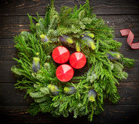 Christmas wreath and candles on wooden background