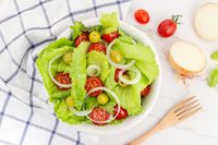 Fresh and healthy salad with lettuce, onion, cherry tomato and olives in a bowl
