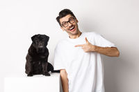 Happy young man showing his cute dog, pointing finger at black pug and smiling, standing over white background