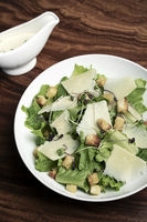 caesar salad with parmesan cheese and croutons on table