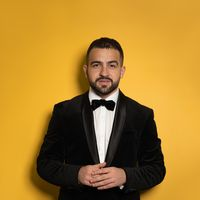 Concentrated handsome man wearing black tuxedo with hands folded looking on camera. Handsome young smiling caucasian man isolated on yellow background. Square crop