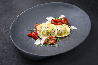 Traditional Italian ravioli pasta offered with parmesan cheese and fried tomatoes as closeup on a modern design plate