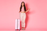 Travelling, holidays and vacation concept. Full-length of confident smiling, attractive asian female tourist, girl making her choise and pointing right, standing with suitcase, pink wall
