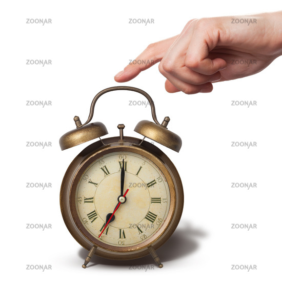 Brown old style alarm clock with hand isolated on white
