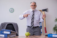 Old male employee holding hatchet in budget planning concept