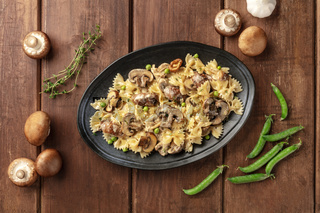 Mushroom and cheese pasta. Farfalle with cremini and green peas, shot from the top with ingredients on a rustic wooden background