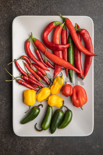 Various types of chili peppers. Chili, habanero and jalapeno peppers. Red, green and yellow hot peppers.