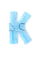 Letter K made from protective medical masks on a white background.