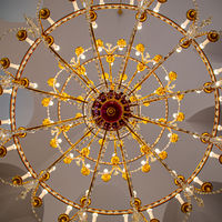 A chandelier from bottom view with colorful ceiling as background