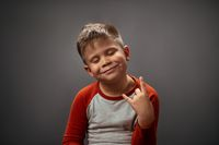 This kid rocks. Fool of satisfied emotions little boy showing ROCK gesture with happy eyes closed. Human emotions, facial expression concept. Facial expressions, emotions, feelings