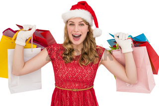 Excited blonde in santa hat holding shopping bags