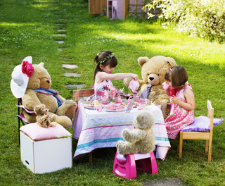Two young girls playing Teddy Bears Picnic in their back garden