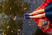 Legs of a young girl near the lake on a plaid in a red cage. Beautiful reflection in the water. View from above.