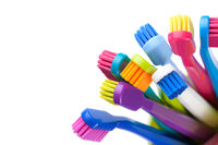 Group Of Colorful Toothbrushes In Cup Isolated