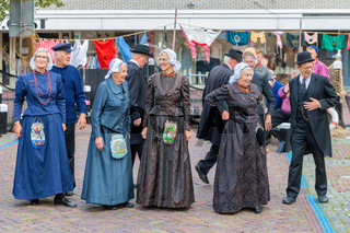 People with traditional clothing and headgear at Dutch local fair