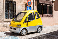 Small yellow electric car parked on street