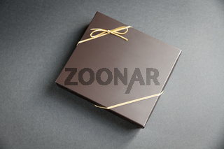 Black gift box with a golden ribbon on black background