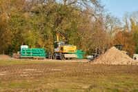 Construction site in Magdeburg city park with excavator and sewage pipes