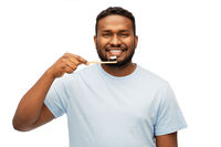 smiling african man with toothbrush cleaning teeth