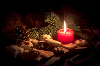 Burning red candle stands between decorated Christmas cookies on a wooden board in front of a dark b