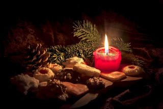 Brennende rote Kerze steht zwischen Weihnachtskeksen dekoriert auf einem Holzbrett