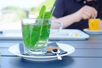 Tea infusion with water mint on table