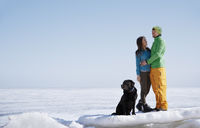Young adult couple outdoors with dog having fun in winter landscape