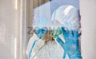 Arzt in Schutzkleidung schaut aus Fenster als Hoffnung Konzept