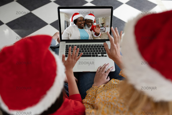 Rear view of woman and daughter in santa hats waving while having a videocall with santa claus and w