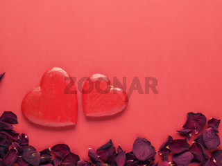 Rustic wooden hearts with rose petals on red background