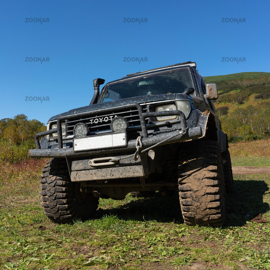 Toyota Land Cruiser Prado on mountain forest landscape in autumn